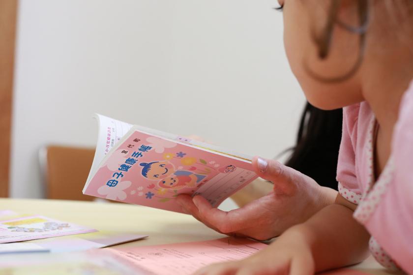 母子健康手帳を持つお母さん