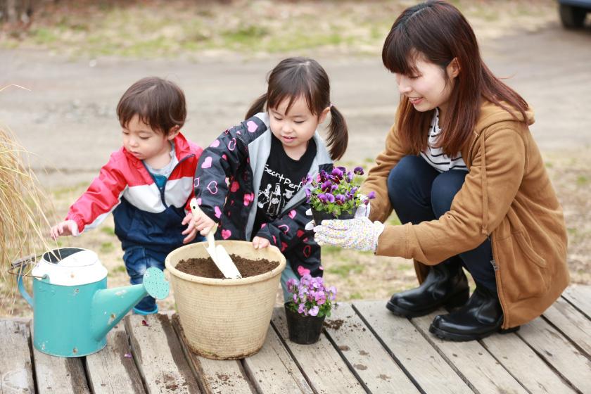 植木鉢に土を入れて花を植える親子