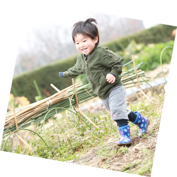 畑で収穫を喜び走る子ども