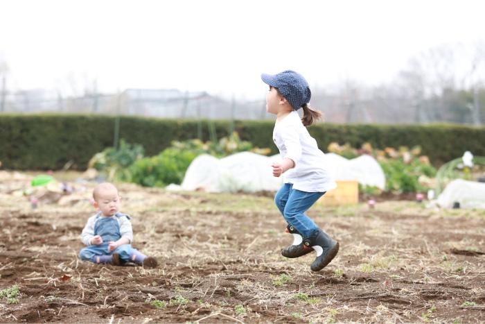 畑ではしゃいで遊ぶ子ども