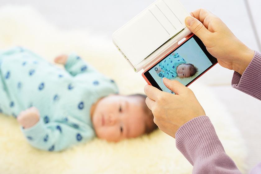 赤ちゃんの写真をスマホで撮影するお母さん