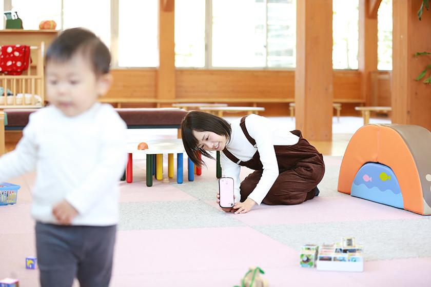 スマホのカメラを床に近づけていつもと違うアングルから子どもを撮影するお母さん