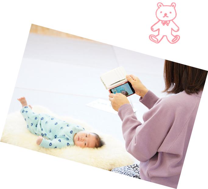 スマホで赤ちゃんの写真をを撮影するお母さん