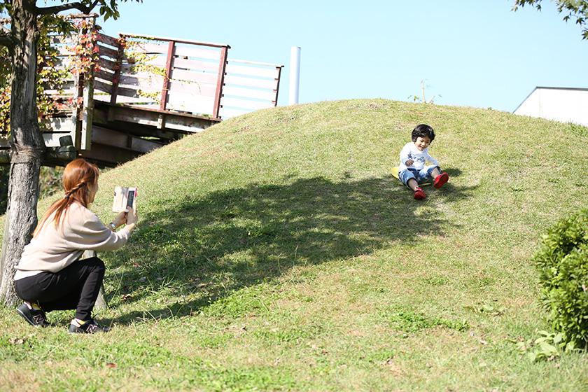 滑って遊ぶ子どもを撮影するお母さん