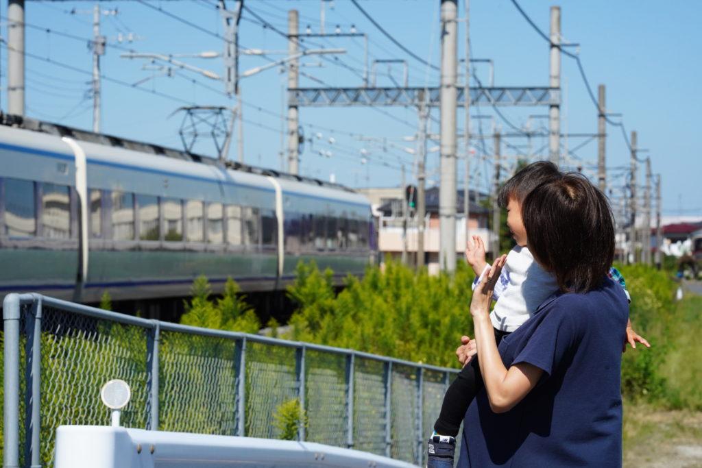 電車を通り過ぎるのを見る親子