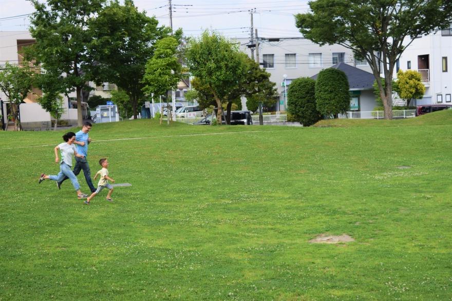 進修館の草原で駆ける親子