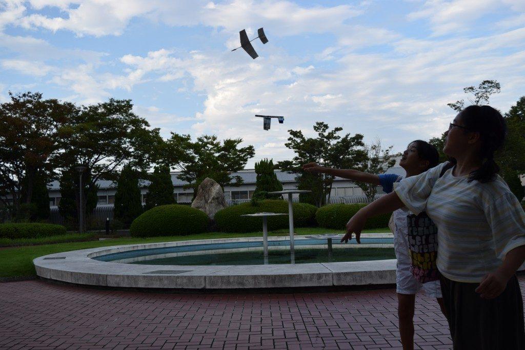 紙飛行機を飛ばす少女
