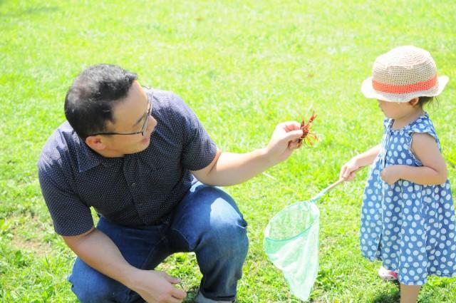 ザリガニを子どもに見せるお父さん