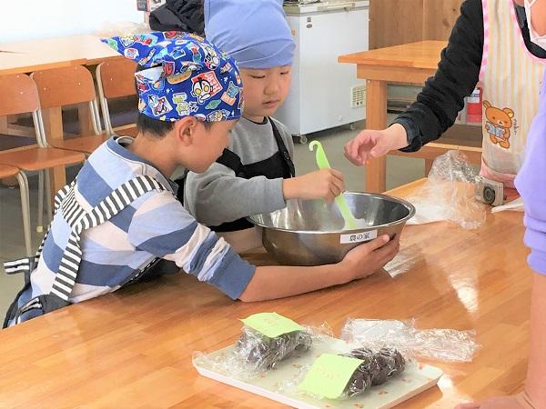 ボウルを支える小学生と粉を混ぜる小学生