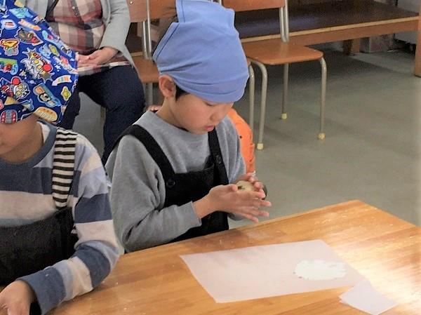 あんこ玉を生地で包む小学生