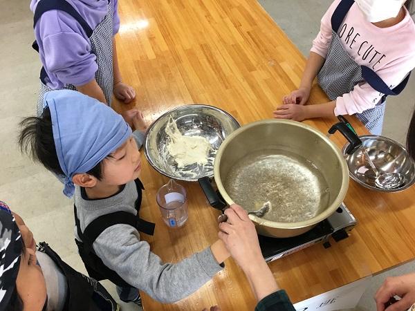 団子の生地を鍋の中へ落とす小学生
